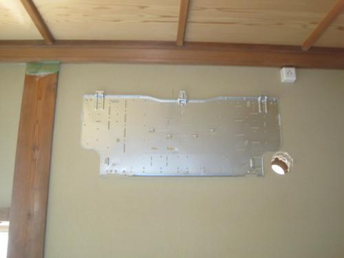 壁に配管用の穴を開けて、室内機の取付部品を固定します