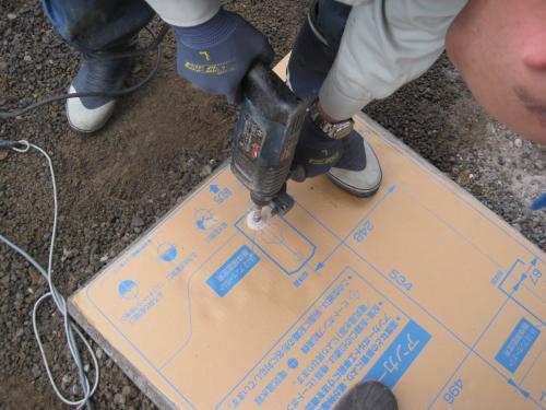 台の基礎コンクリートへ型紙をあてて アンカーボルトの穴を開けます