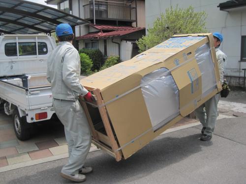 エコキュートをトラックから降ろして運びます